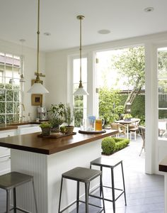 A white clean kitchen that opens up to the backyard patio