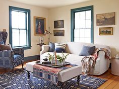 The home's remote location renders window treatments unnecessary. Mid-1800s homespun blankets cover the wing chair, ottoman, and hardwood floor; the slipcovered sofa is from ABC Carpet & Home. The candle holder is from The Future Perfect. The windows are painted Everard Blue and the walls are Montgomery White, both by Benjamin Moore. #livingrooms