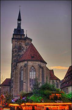 The twin towers of the Stiftskirche on Schillerplatz, overlooking the Christmas market (Weihnachtsmarkt) at dusk.