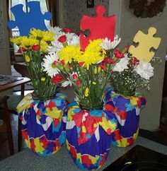 Centerpieces made with half gallon mason jars.  Autism themed bandanas wrapped around them and held in place with rubber bands.  Spray painted foam puzzle pieces for bouquet decor.