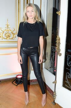 Gigi Hadid wearing all black in leather pants paired with pointy-toe nude pumps.