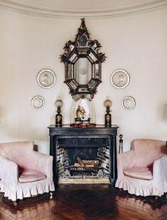 Dernière visite de l'atelier d'un peintre mondain Des Miroirs en verre de Venise du XVIIIe siècle et des portraits de famille en médaillon animent l'un des salons. La cheminée est ornée d'une pendule d'époque Restauration.
