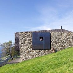 Farmstead Next to the Chapel - An enormous frame surrounds a little window in the reconstructed stone wall that flanks this holiday home in northern Italy by architects Bergmeisterwolf