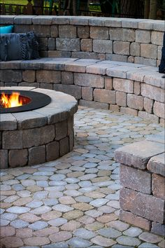 Built-in tumbled stone seat walls set the perfect stage for a family s'mores cook-off. Multi-tone cobbled pavers add a coordinating whimsical touch. Don't forget pillows and throws to complete the look and keep everyone snuggly and warm! Fire Pit Backyard, Backyard Patio, Backyard Landscaping, Garden Fire Pit, Backyard Seating, Outdoor Rooms, Outdoor Living, Outdoor Decor, Wood Fire Pit