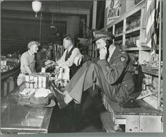 Pilot and actor Jimmy Stewart chatting on the phone in his father's store after returning from the war, 1945