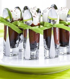Individual chocolate mousse parfaits topped with fresh whipped cream and served in a tall shot glasses. Spoons are tied to each glass.