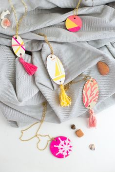 Charming geometric + nautical wood pendant necklaces look fabulous with colorful tassels swinging on a gold chain. Perfectly adorable summer sundress jewelry.