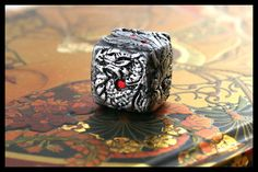 The second in my series of molded dice, this one has the appearance of a carved dragon. The dragon wraps around all six sides. The final photo shows the