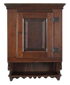 Sold $15,000 Pennsylvania walnut hanging cupboard, ca. 1770, the molded cornice over a raised panel door with original wrought iron hardware, above an op...