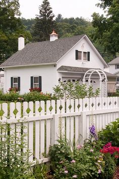 This Country home has it all. White picket fence, window boxes, country flower garden, & garden archway.