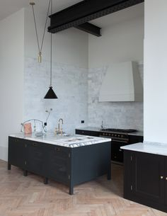 An extended backsplash of Carrara marble is paired with white walls and exposed industrial beams.  Carrara marble is also used on the counters and the island is topped with more dramatically veined arabescatto marble.