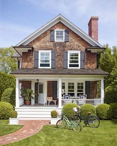 Quaint shingled cottage with covered porch and brick walkway.