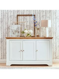 Ideal Home Wiltshire 3 Door Large Sideboard in Cream - this generously sized Wiltshire sideboard from Ideal Home measures 138 cm in width, providing plenty of room behind its panelled doors for stowing away everything from dinner sets to DVDs. An internal shelf is adjustable and removable for flexible storage, and its rural charm comes from a chunky style, shaped plinth and top, dainty metal handles and country cottage cream colour that helps the rustic oak-effect top stand out b...