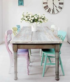 Shabby dining table with multi colored pastel chairs gives this room a vibrant and inviting feel.