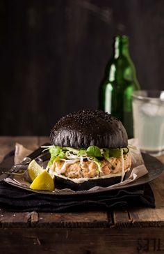 salmon burger on a black brioche bun  hamburguesa de salmón en un pan brioche negro