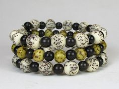 * * Coiled memory wire bracelet with natural cream and yellow salwag seed beads, 8mm and 6mm * Accents of ebony wood beads, about 5mm * Memory wire has a 2 1/4 diameter with 3 rows - 3 line  *  This i