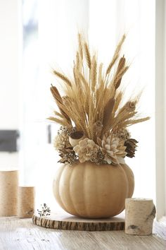 Cut tops and center out of pumpkins and fill with wheat and pine cone arrangement