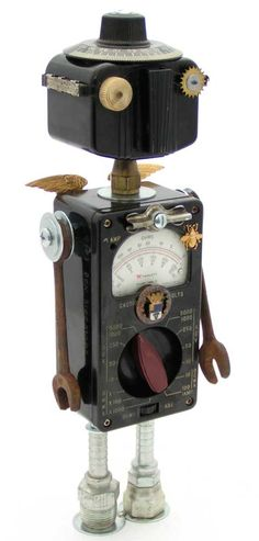 """""""Ecce Ohmo""""   Height: 14""""   Principal Components: Ohm meter, Baby Brownie camera, wrenches, bakelite machine dial, clock gear, hose fittings, jewelry"""