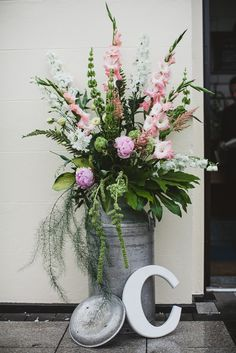 large milk churn filled with flower arrangement & painted wooden initial letter - Image by Connor McCullough - A vintage inspired wedding in Northern Ireland with lace wedding dress, pink and green colour scheme and photographs by Connor McCullough wedding photographer