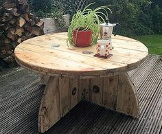 There we have another pallet cable spool table for patio Its texture and form is amazing. Its beauty is in its simplicity. The base of the table is different from common wooden cable reel tables. It is interesting and makes the table well balanced and durable.