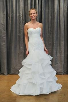 Judd Waddell Carola is a strapless tulle fit and flare gown. It features a draped bodice and horsehair trimmed cascades that give this gown a timeless look. This gown came from a designer bridal boutique and is in excellent condition. Judd Waddell Carola is Ivory and a size 10.