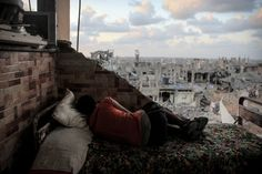 A boy sleeps amid the rubble of his destroyed house in Gaza Strip on Sept. 1, 2014.
