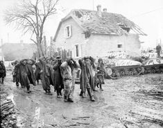 German soldiers captured in Bischwiller, Alsace-Lorraine, under the escort of soldiers of the US 75th Infantry Division. Behind them by the house there are two American M4 Sherman tanks.