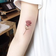 Red rose tattoo on the right inner arm.