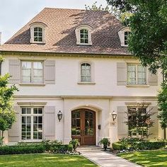 Beautiful French home with shutters and double front door. #homedesigns homechanneltv.com