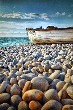 Reminds me of the beaches along Slea Head in Ireland. Beautiful rounded rocks along the shore for as long as the eye can see. Beach pebbles & rowboat + beautiful