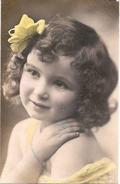 Meisje met gele strik en blauwe sierraden