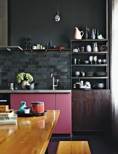 The kitchen cabinets benefit from a pop of rosy color, a custom hue. Fehrentz designed the steel-and-wood storage unit.  Photo by Peter Fehrentz.