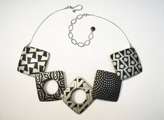 Square Necklace Black and Ivory by Louise Fischer Cozzi. Using shades of black and silver, the artist has created this necklace in polymer clay. Each geometric component is playfully decorated in various designs. Chain is adjustable from 16.5
