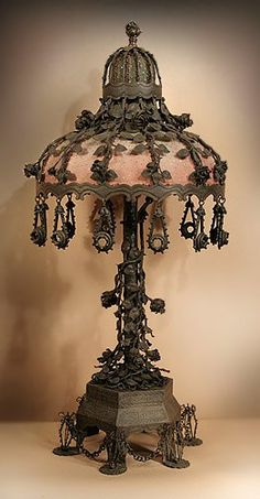 """Steampunk """"THE ROSE GARDEN"""": A handmade iron table lamp with matching shade. Wire cages stand on the feet of the base, connected by chains. In the stem are dozens of thorned vines and roses. The shade has rose stems trailing down to its rim to oval shaped drops, each with a sparkling jewel center."""