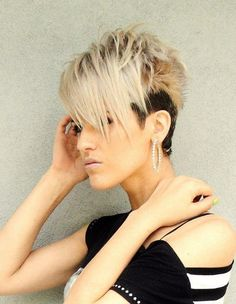 Razored crop haircut with long blonde piecey side swept bangs and short dark shaved sides hairstyle