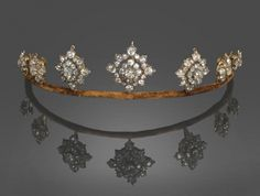 Late Victorian Diamond Tiara, comprising seven graduated lozenge shaped old cut diamond clusters, each held in screw fittings on the frame of brown velvet, all cluster sections detach and can be fitted to a necklace, with bars linking the diamond pieces, to a white trace chain, length 39cm additionally there are two fittings to allow the principal diamond lozenges to be worn as brooches, the whole in a case by D & J Wellby Ltd, Garrick St, London