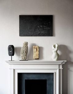 Minimalist fireplace mantle styling featuring multiple stone sculptures and dark artwork - Home Decor Details