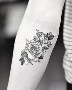 Peony and rose tattoo on the right inner forearm.
