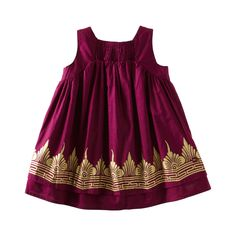 "There's a lot of gold in Bali fabric, especially ceremonial clothing. In fact, they'll actually paint the fabric with gold. We took this idea to heart and created our own ""painted"" golden temple border on a crinkle cotton baby dress. Bloomers on sizes 6-24 months. Imported."