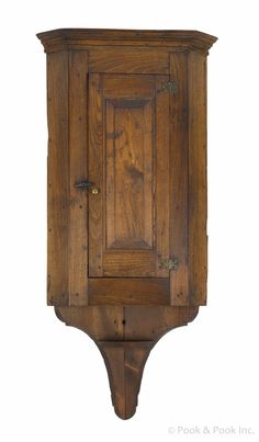 "Pook & Pook. April 25th & 26th 2014. Lot 609. Pennsylvania walnut hanging corner cupboard, early 19th c., with a raised panel door & fishtail base, 55 1/2"" h., 22 3/4"" w.  Good condition. No apparent damages or repairs.  Removed from a home in Columbia, Pennsylvania. Estimated: $3000 - $4000."