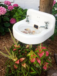An old pedestal sink gets a new lease on life as a birdbath in this cottage garden.