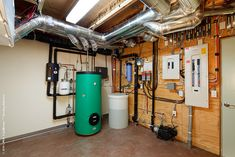 Workshop/mechanical room with solar hot water storage tank (green), rainwater tank (white), and electrical panels