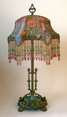 This is a hand painted, detailed, ornate early 1900s metal lamp base which holds a Haight-Ashbury Beehive lampshade in colors of pink, green and teal. Antique hand-dyed cut velvet and gold metallic lace overlay the panels and a pair of vestment appliqués in vibrant pink, gold and green adorn the front and back.    Hand beaded fringe with Swarovski crystals pick up all the brilliant colors of the shade. A jeweled pull chain turns on the lamp.