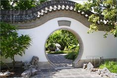 Picture of A circular gate to a lush oriental garden.