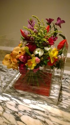 Brightly coloured mixture of flowers. The bouquet stands inside a Perspex box. This goes well on round tables Table Centerpieces, Centrepieces, Table Decorations, Berkeley Hotel, Hand Tied Bouquet, Table Centers, Party Fashion, Spring Flowers, Orchids