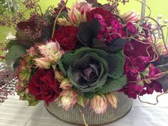A jewel-toned arrangement made by one of our own (props to Nikki) for a personal event. Rustic tin planter with kale, Hearts roses, curly willow, stock, blushing bride, seeded eucalyptus, hydrangea, and smokebush.