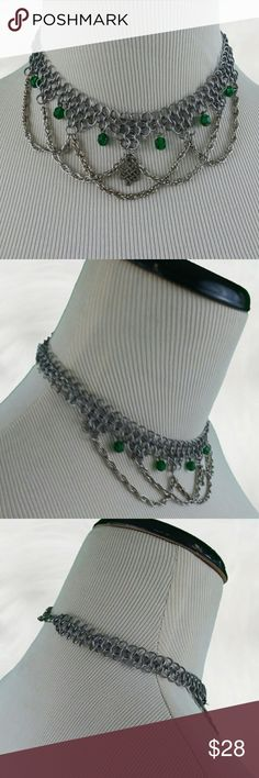 "VINTAGE Silver Chain Mail Swagged Choker What a cool choker. Linked silver tone rings in a chain mail style make up the choker and twisted silver tone rope chains hang is seats  with green faceted beads between each swag. A tiny silver tone Celtic looking infinity type symbol hangs from the very center. It measure 15"" in length with a lobster claw clasp and has a drop if 2 1/2"". In good vintage condition, but there is a small amount of discoloration if the chain. Vintage Jewelry Necklaces"