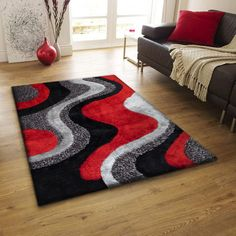 Bright Black Gray Red shag rug made with long lasting use and soft comfort materials that you want to lay on  and Sink your body in to. The Backing is made with cotton backing that is made to be scratch free for your hardwood or tile floors. The thickness is about one inch to two inch. It comes in different size and shape from 2' x 3', 4' x 6', 2' x 8', 5' x 7', 8' x 11' price range $50 to $700 http://rugaddiction.com/collections/designer-shag/products/black-grey-with-red-shag-area-rug