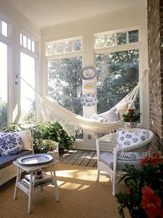 sunroom with blue and white furniture and white hammock