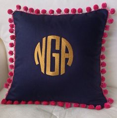 This is a navy cotton pique pillow cover embroidered with a gold circle monogram ( option G) and trimmed with hot pink pom poms. This is shown in